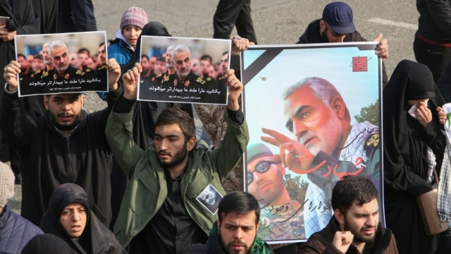 Iranians hold posters of Iranian Revolutionary Guards Major General Qassem Soleimani during a demonstration in the capital Tehran against the killing of the top commander in a US strike in Baghdad. (Photo by ATTA KENARE/AFP via Getty Images)