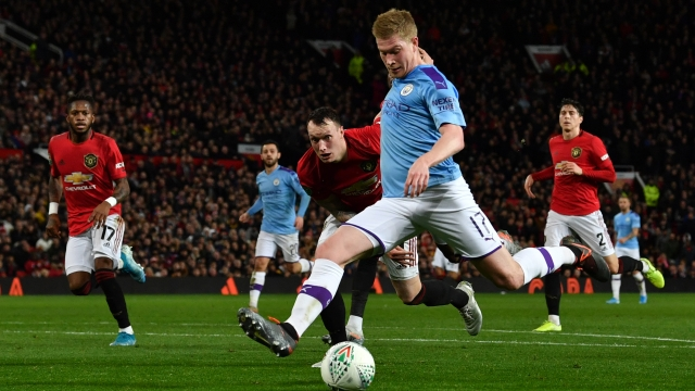 Manchester City's Belgian midfielder Kevin De Bruyne strikes the ball to shoot for City's third goal, given as an own goal by Manchester United's Belgian-born Brazilian midfielder Andreas Pereira