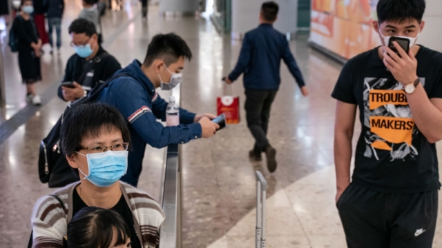 People wearing face wait at the arrival hall at West Kowloon Station on January 23, 2020 in Hong Kong, China
