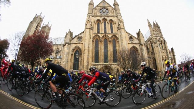Riders pass a church at the start of the first stage of the 2016 Tour de Yorkshire from Beverley to Settle