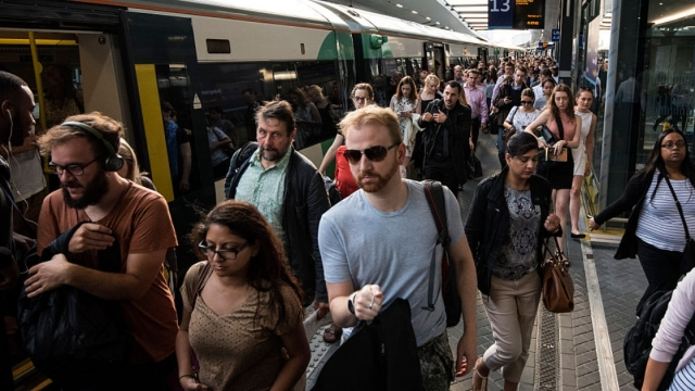 Commuters disembark a rush hour Southern rail train at London Bridge