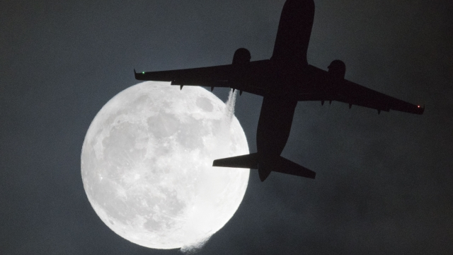"""A plane flys in front of a """"super moon"""" or """"wolf moon"""" on its approach to London Heathrow Airport"""