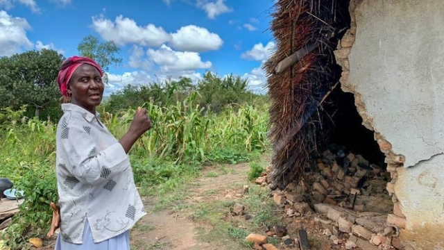Article thumbnail: A woman stands by the remains of a building destroyed by Cyclone Idai (Photo: Idzai Murimba/Tearfund)
