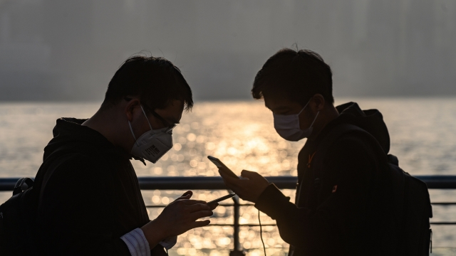 People wear face masks to protect themselves against coronavirus in Hong Kong, where a UK tech firm has offered free access to English-speaking schools closed by the virus