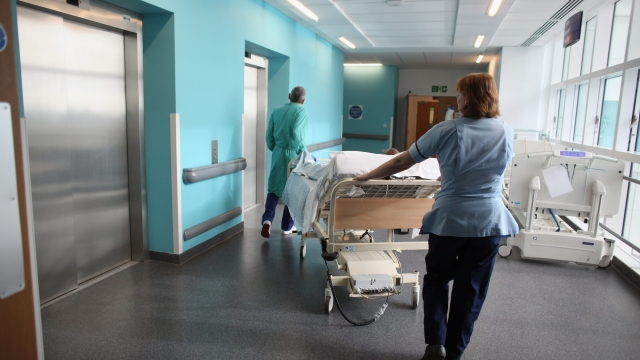 Nurses moving bed around in hospital