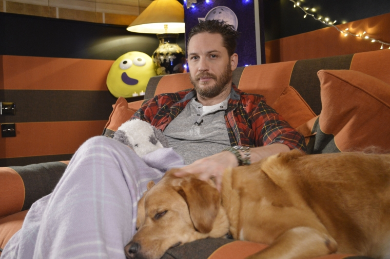 Actor Tom Hardy cuddles up to his dog during his recording of CBeebies' Bedtime Stories (Photo: BBC/PA Wire)