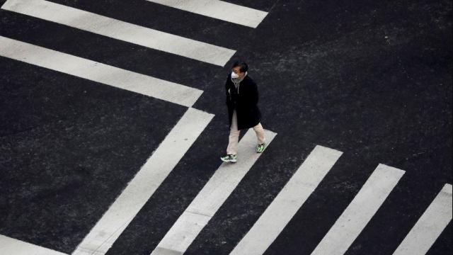 A man wearing a mask to prevent contracting the coronavirus walks on a zebra crossing in Seoul, South Korea, February 20, 2020. (Photo: REUTERS/Kim Hong-Ji)