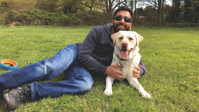 Amit lays across the grass with guide dog labrador Kika