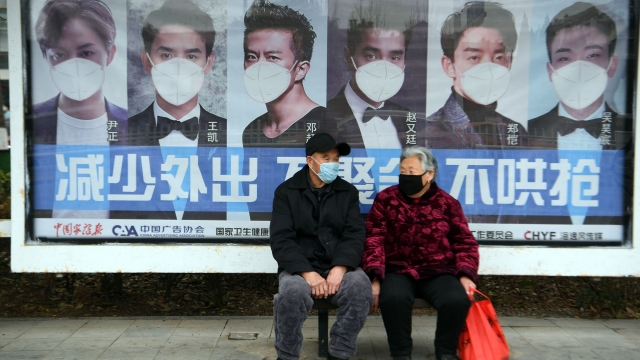 A man and woman sit in front of a poster reminding citizens to wear face masks in Bozhou, China (Photo: AFP/Getty Images)
