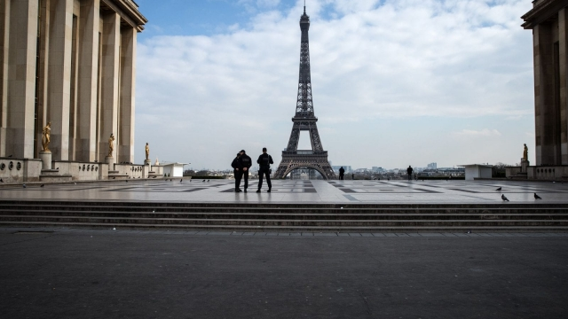Policemen stand on the Trocadero square near the Eiffel Tower in Paris on March on 17, 2020, while a strict lockdown comes into in effect in France to stop the spread of COVID-19, caused by the novel coronavirus. France's 67m people are allowed out of their homes only to buy groceries