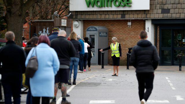A staff member enforces social distancing rules at a Surrey supermarket