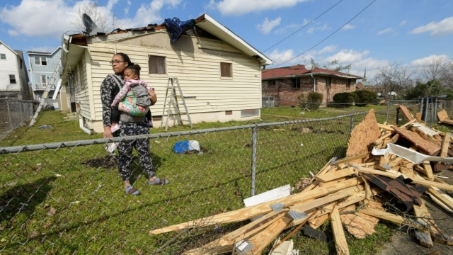 Article thumbnail: Dominique Hammond and her daughter Analise Hammond are seen outside their home in North Nashville following devastating tornadoes