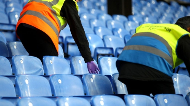 Stewards clean seats at Selhurst Park before a Crystal Palace match - all fixtures are now postponed until 3 April at the earliest (Photo: Getty)