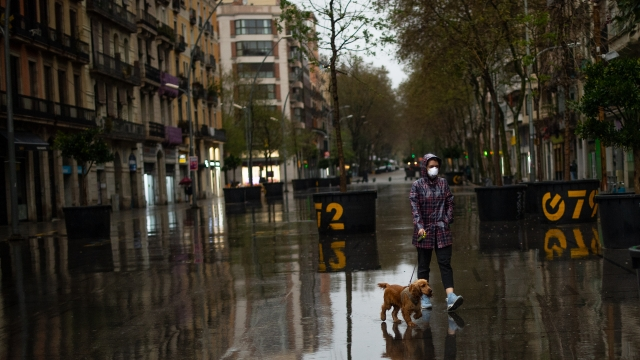 A woman wearing a protective mask walks her dog on an empty street on March 16, 2020 in Barcelona, Spain. As part of the measures against the virus expansion the Government has declared a 15-day state of emergency (Photo by David Ramos/Getty Images)