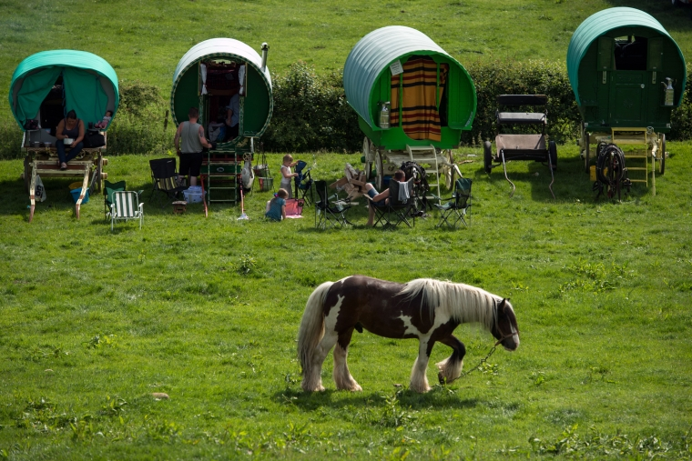 People sit outside traditional gypsy caravans on the opening day of the annual Appleby Horse Fair, in the town of Appleby-in-Westmorland, north-west England on June 7, 2018. - The annual event attracts thousands of travellers from across Britain to gather and buy and sell horses. (Photo: OLI SCARFF / AFP)