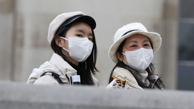 Two women walk through London's Trafalgar Square wearing protective facemasks as the coronavirus outbreak spreads (Photo: PA Wire)
