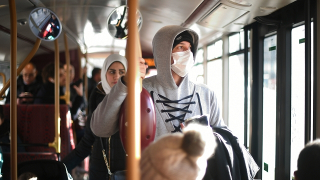 The number of people diagnosed with coronavirus in the UK has risen to 51. Pedestrian wears a mask in London
