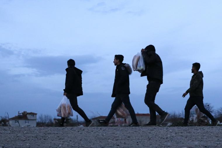 A migrant man covers his face as he walks near the Turkish-Greek border (Photo: AP Photo/Darko Bandic)