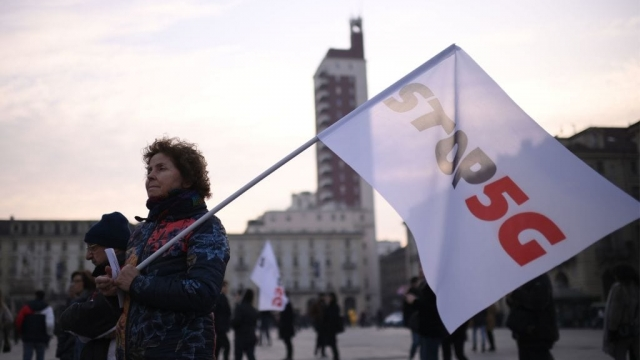 """A demonstrator holds a placard reading """"Stop 5G"""" during a demonstration against the 5G net, the new technology for mobile and internet communications at Piazza Castello in Turin, on January 25, 2020. (Photo by Marco BERTORELLO / AFP) (Photo by MARCO BERTORELLO/AFP via Getty Images)"""