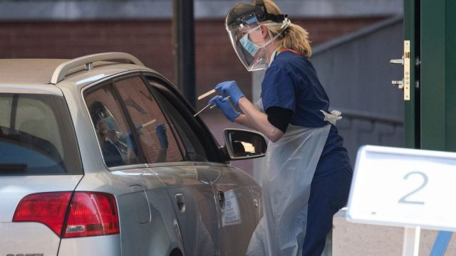 A medical worker takes a sample from a person at a drive-through testing facility for NHS workers in London, England