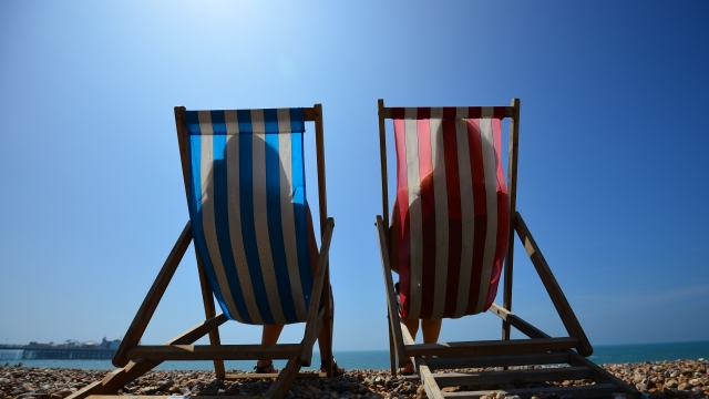 People relax in deck chairs on the beach in Brighton on July 18, 2014, as parts of the country were expected to experience the hottest day of the year so far and the Met Office issued a heatwave alert for southern England and the Midlands