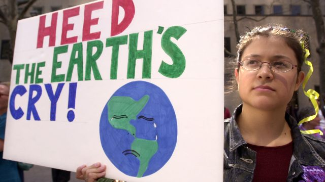 A protester holds a sign at an Earth Day rally April 22, 2001 in front of the United Nations in New York City