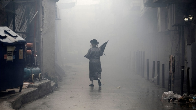 An Ultra-Orthodox Jewish man walks down a street through the smoke from burning leavened items during the Srefat Chametz ritual on March 30 2018