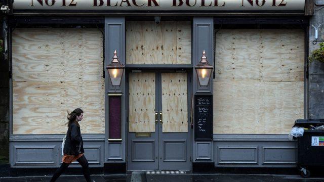 People walk past a closed pub in The Grassmarket, Edinburgh, Scotland on March 26, 2020