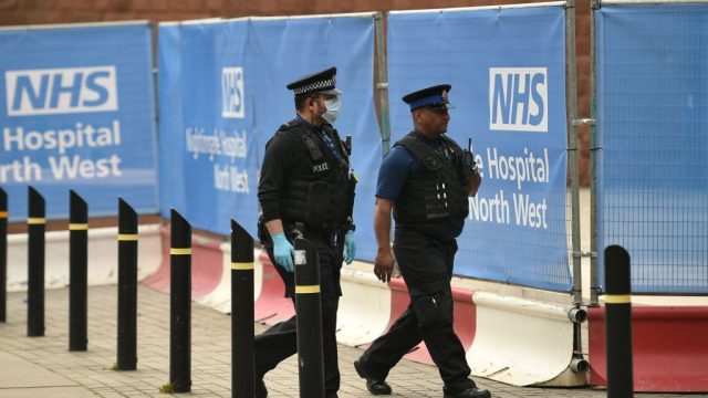 "Police officers patrol outside Manchester Central Complex as the ""Nightingale Hospital North West"" is prepared (Photo: Getty)"