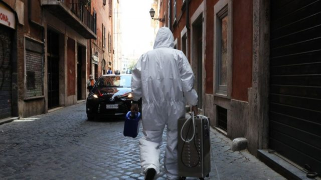 A technician who has just sanitized a shop in central Rome walks down an alley at the end of his job on 15 May 2020 (Photo: Getty)