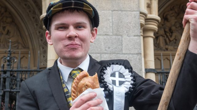 A man eats a Cornish pasty as he attends the St Piran's Day march (Photo: Matt Cardy/Getty Images)